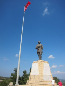 Turkish flag and stature of Ataturk at the spot where he was shot and saved by his pocket watch