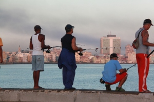 Local men fish along the Malecon at sunrise.