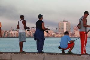 Local men fish along the Malecon at sunrise.