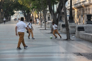 Children play some soccer along the Prado in the early morning
