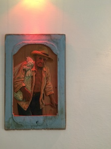 a Trinidad artist carves soulful locals on panels of wood.